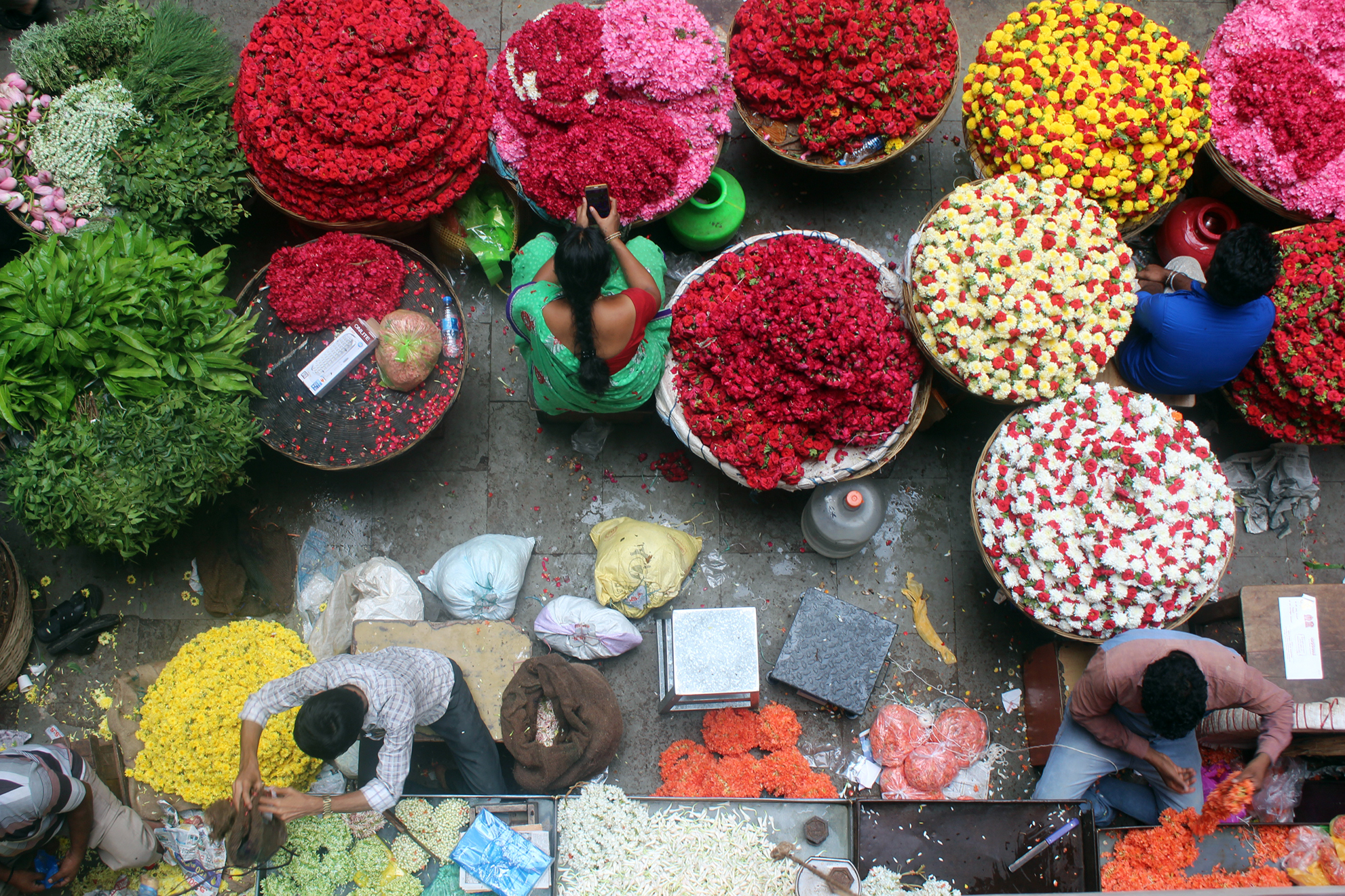 Looking down from above on people sorting flowers in a market