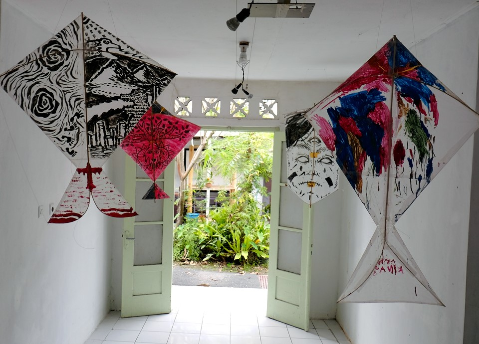 Painted kites hanging in a white room