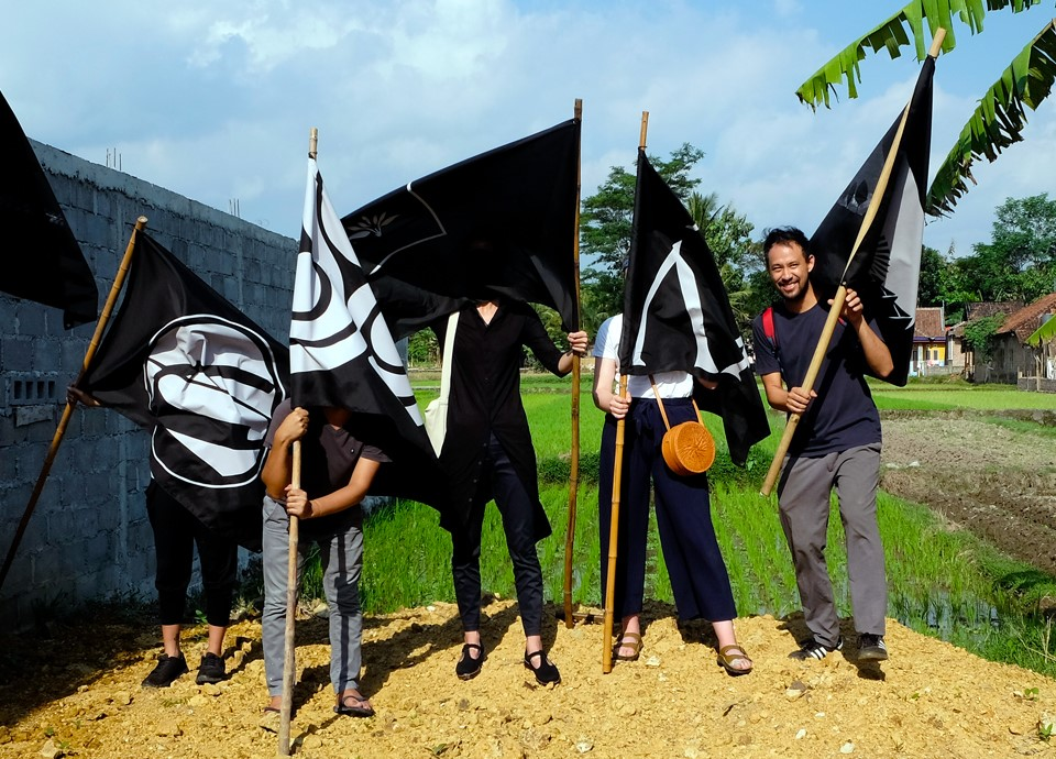 Four people standing on a mound of dirt holding black flags