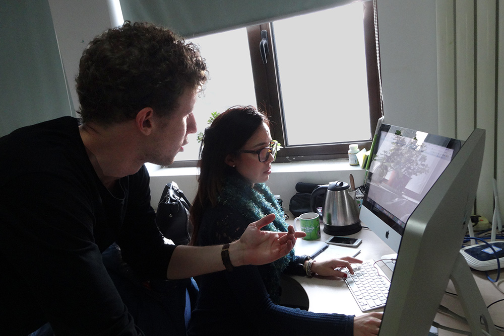 Edward talking to a colleague who is sitting at a computer