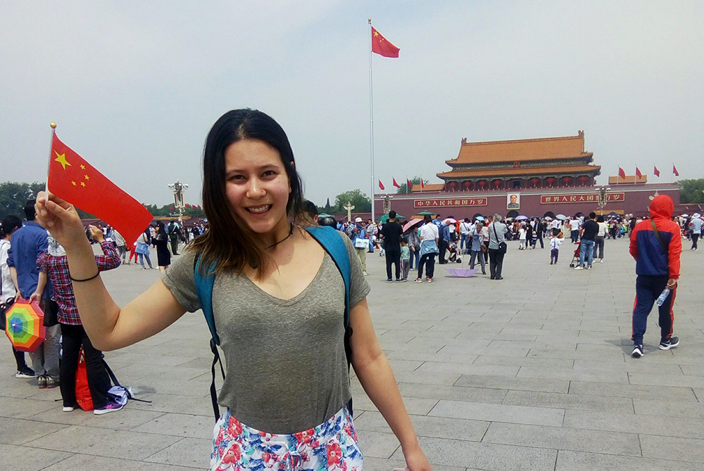 Emily Wilby waving a small Chinese flag in Tiananmen Square