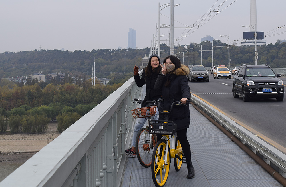 Emily Wibly and a friend sitting on bikes on a highway overpath