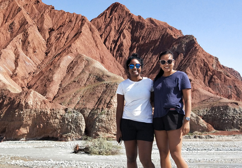 dhaxna standing with a friend in front of a red -clay mountain