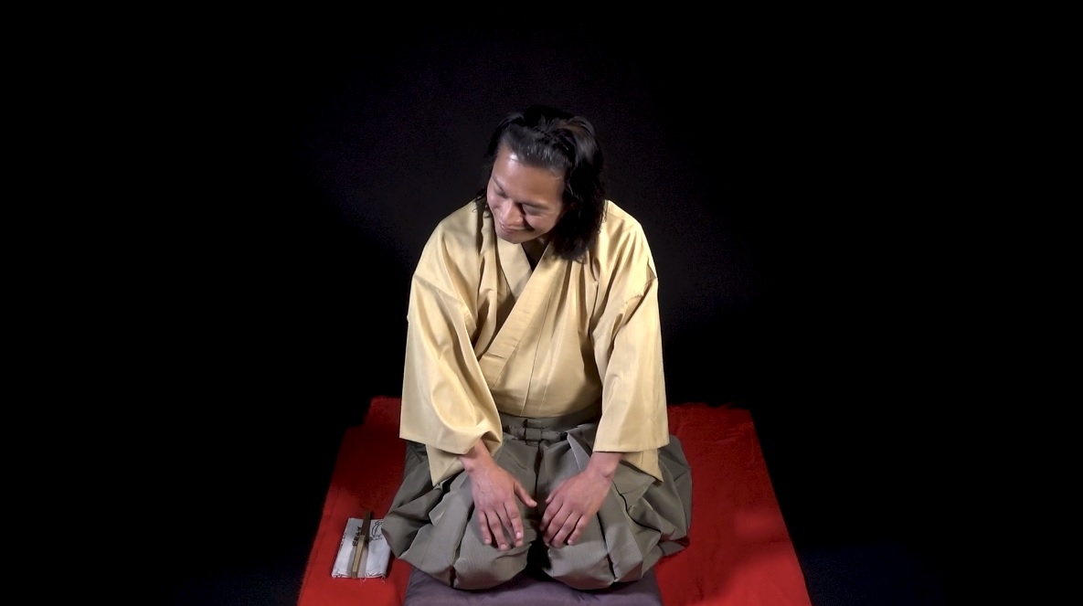 Hiroshi kneeling on a mat wearing traditional Japanese clothing