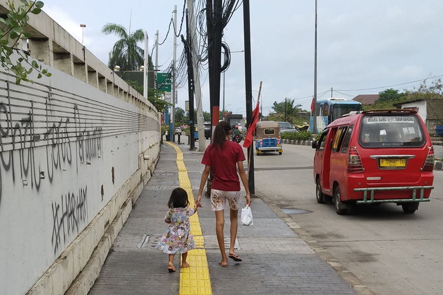 A woman and a child walking down the street