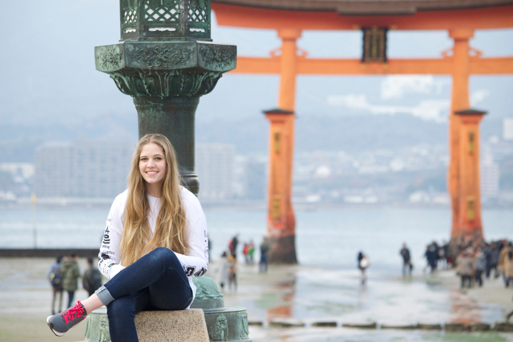 Woman sits in front of Japanese gate while on a Japan study grant