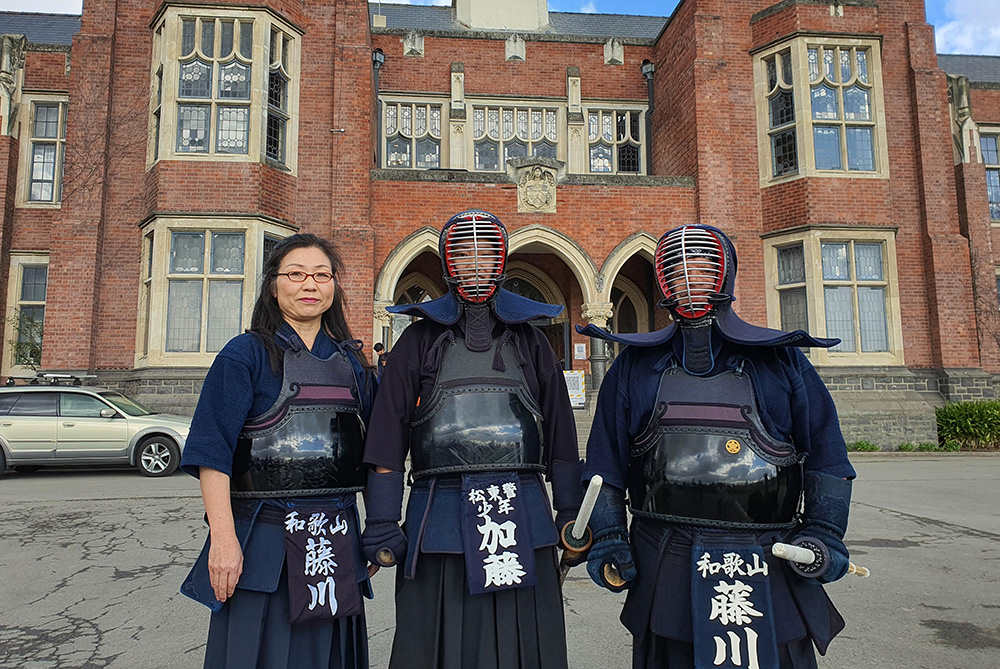 Three people wearing kendo protective clothing and face masks