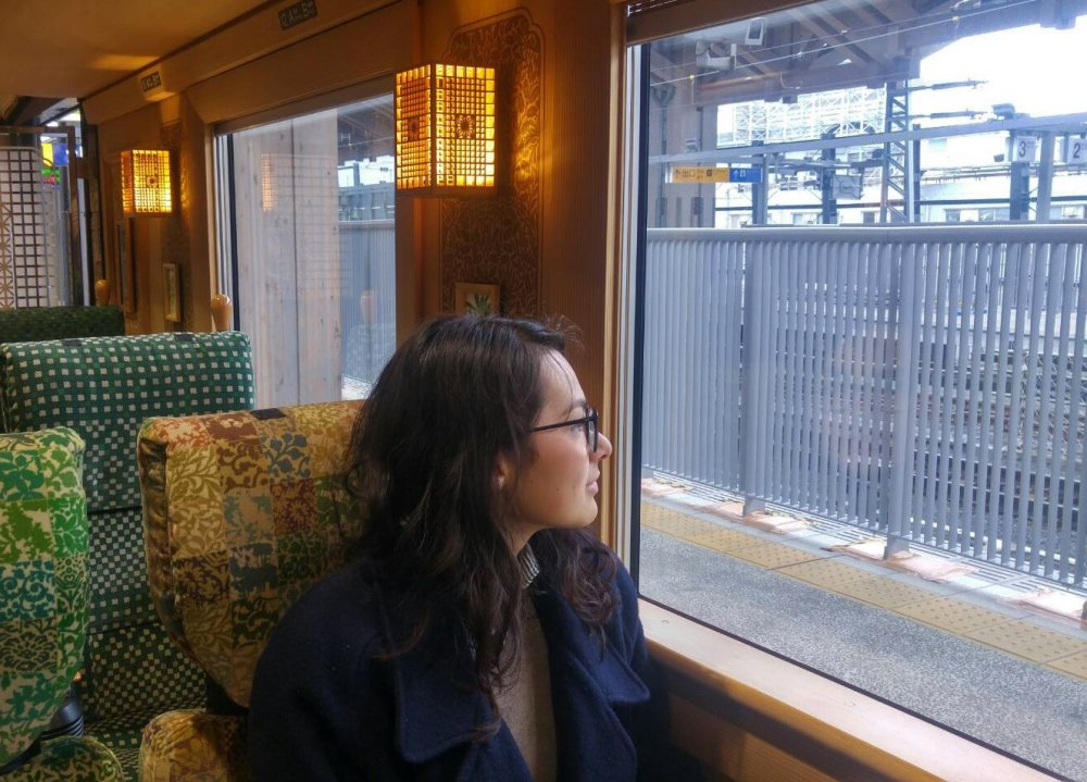 woman sits in train, looking out window