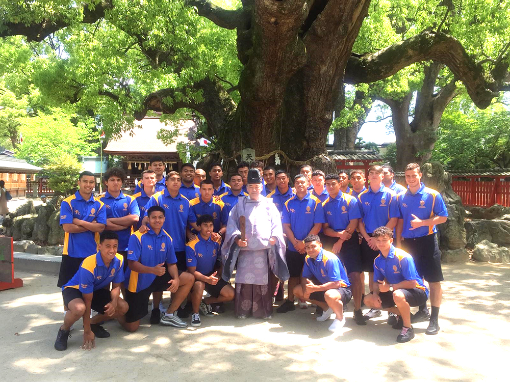 The team posing beneath a large tree with a Shinto priest