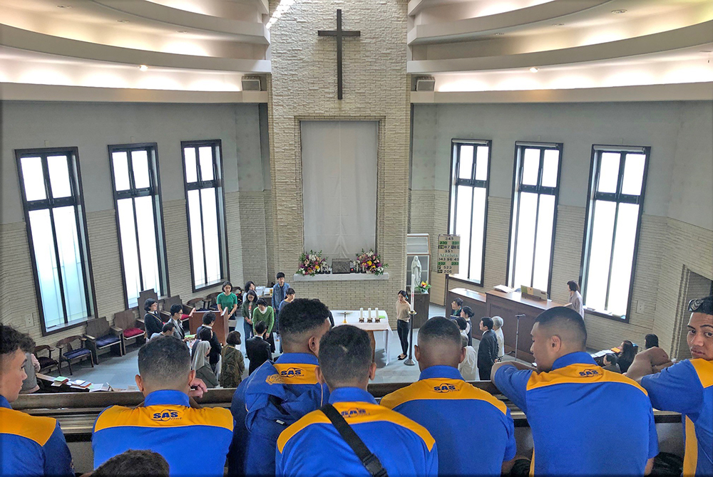 A view looking over the shoulders of Saint Peter's College students into the transept of a church