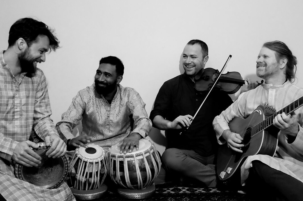 The Wellington contingent of Shades of Shakti - Thomas Friggens, Chetan Ramlu Tristan Carter and Justin 'Firefly Clark sitting on the ground with their instruments