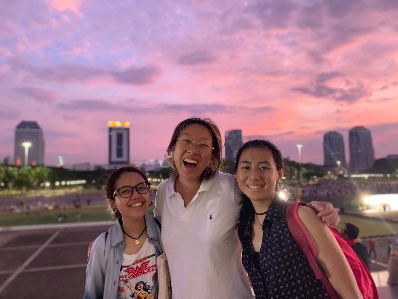 Sherry with two Indonesian students with a pink sunset in the background