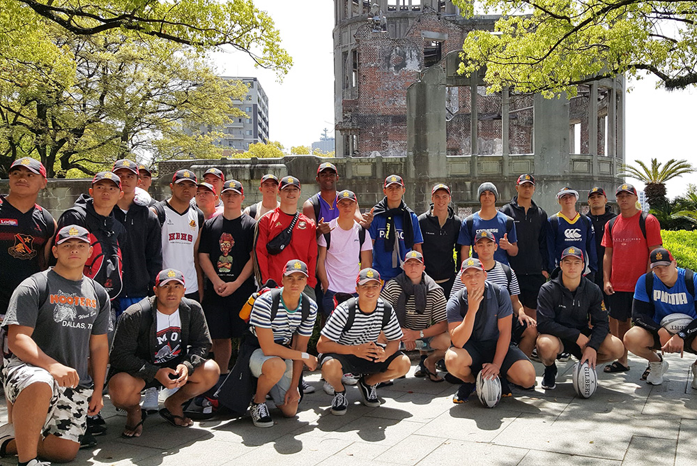 The team crouching down in front to the Genbaku Dome in Hiroshima