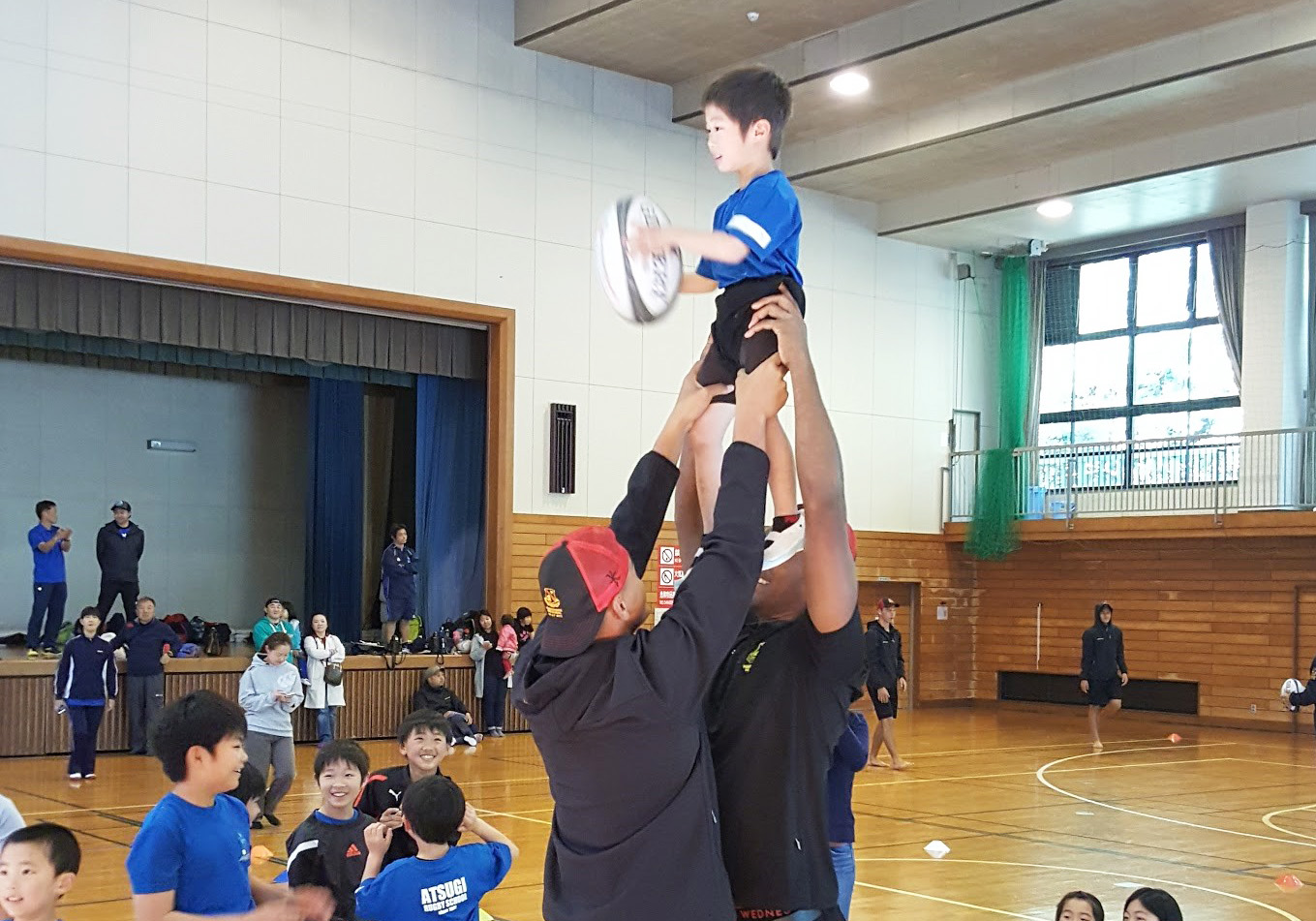Two Hamilton Boys Rugby players lift a young boy into the air to catch a rugby ball