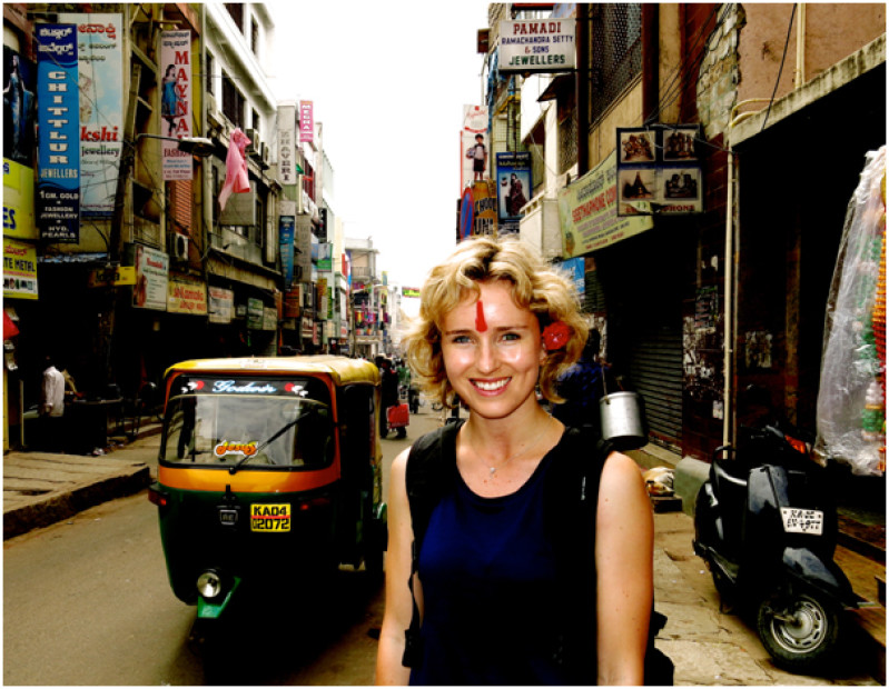 Journalist Isobel Ewing in a street in Bangalore with a tuktuk beside her