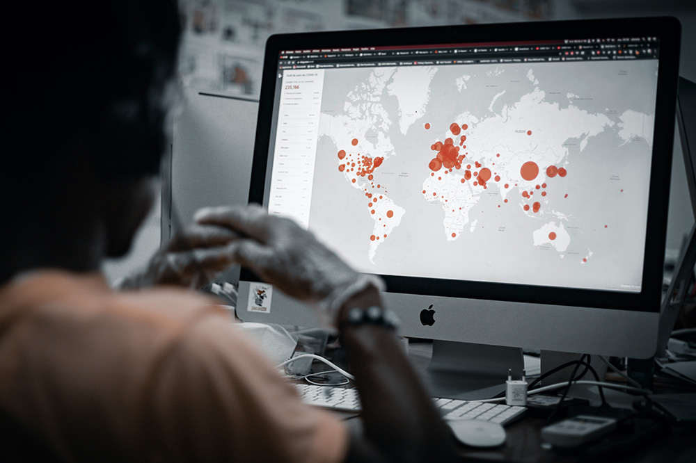 A man sitting at a computer looking at a graphic depicting the spread of COVID-19 around the globe