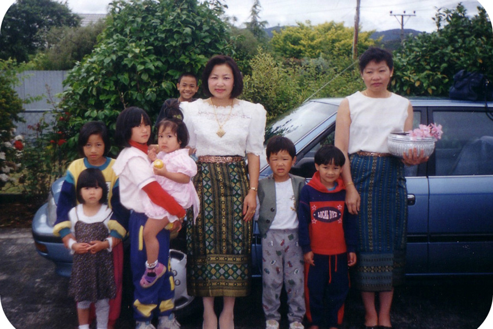 A family from Laos standing in front of their car in Wainuiomata