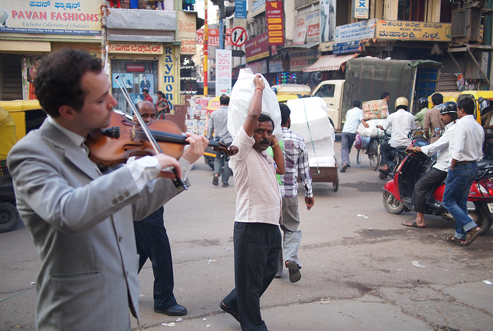 A man carrying a sack on his sholder watches Tristan play the violin on a street in Bangalore